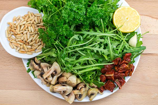 Und das braucht ihr für ein veganes Rucola-Pesto: Rucola, Petersilie, geröstete Pinienkerne, Champignons, getrocknete Tomaten, Zitrone, Olivenöl, Salz und Pfeffer.
